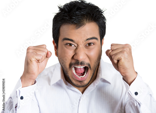 Angry, mad young man with fists in air, screaming at someone