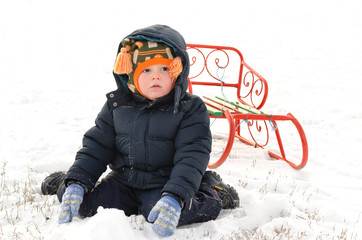 Small boy kneeling in the snow with a sled