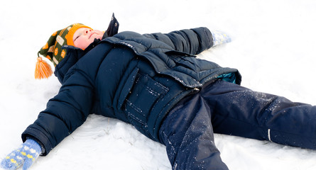 Happy little boy making snow angels in the snow