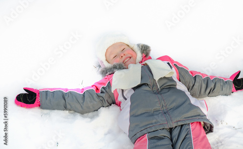 Laughing little girl lying in the snow