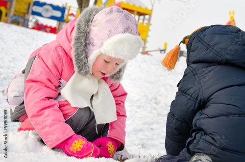 Cute little girl gathering snowballs in the snow