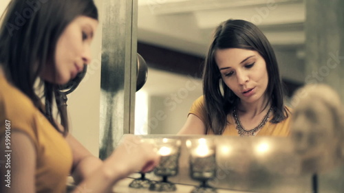 Beautiful sad, pensive woman standing by the mirror