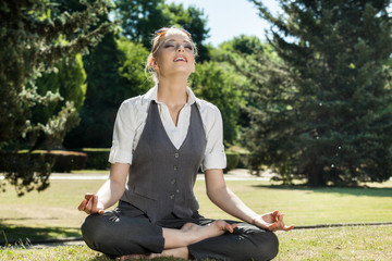 Beautiful woman meditating in the park