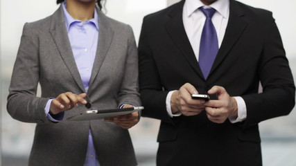 two businesspeople with smartphone and tablet pc