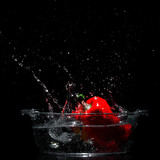 Falling red sweet pepper to tank with water