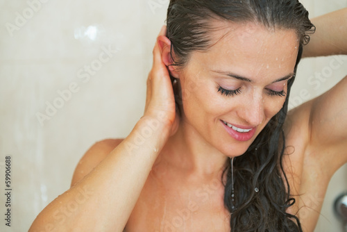 Portrait of young woman washing in shower