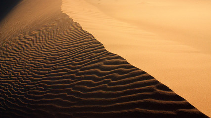 Sand texture with light and shadows and wind-created waves