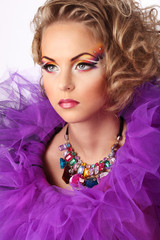 Portrait of young caucasian female with bright colorful makeup