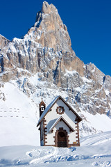 Small church in front of peak in Passo Rolle, Italy