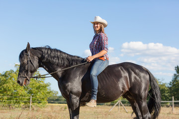 Cowgirl Riding a Black Stallion Horse