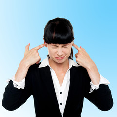 Female employee covering her ears