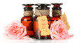 bottles of oil and roses isolated on white