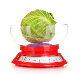 green cabbage in a kitchen scales isolated on white
