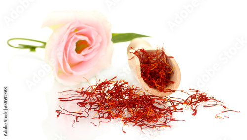 stigmas of saffron in wooden spoon isolated on white close-up