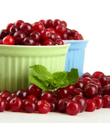 Ripe red cranberries in bowls, isolated on white.