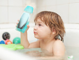 kid bathes with shampoo  bottle