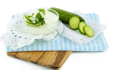Cucumber yogurt in bowl, on wooden board, isolated on white