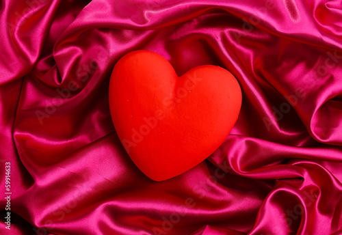 Decorative red heart, on color fabric background