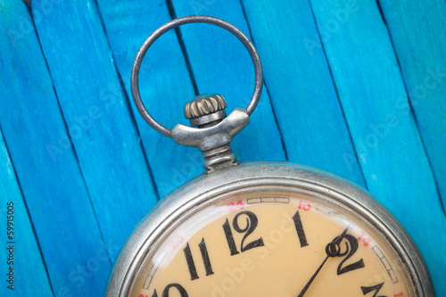 close up of old style pocket watch on blue wooden backround