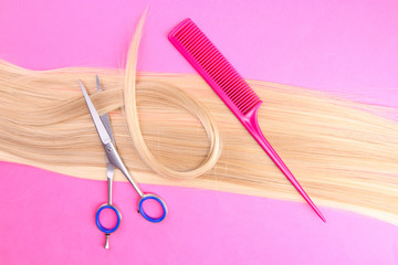 Long blond hair with comb and scissors on pink background