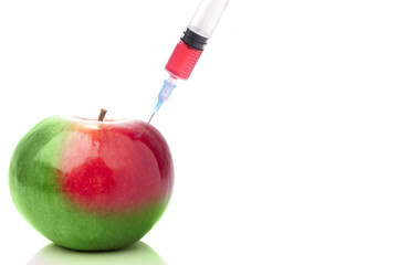 Apple in two colors with a syringe. Concept for GMO.