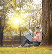 Girl reading a book and enjoying the sunny day in a park seated
