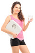 Beautiful woman holding glass of water and weight scale