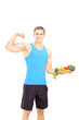 Young male holding plate full of vegetables showing his muscles