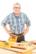 Middle aged male carpenter standing behind working table