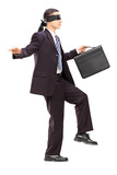 Blindfolded young businessman with briefcase walking