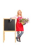 Female gardener standing next to black table and holding flowers