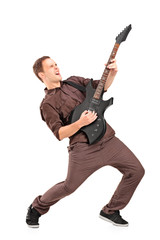 Full length portrait of a young man playing on electric guitar