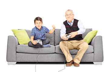 Senior man sitting on a couch  playing video games with nephew