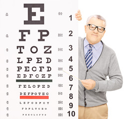 Senior man standing behind eyesight test pointing with a stick