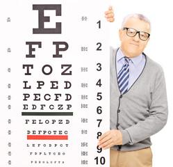 Senior man standing behind eyesight test