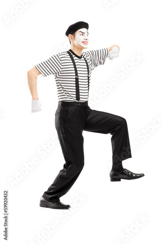 Full length portrait of male mime artist simulate walk on a rope