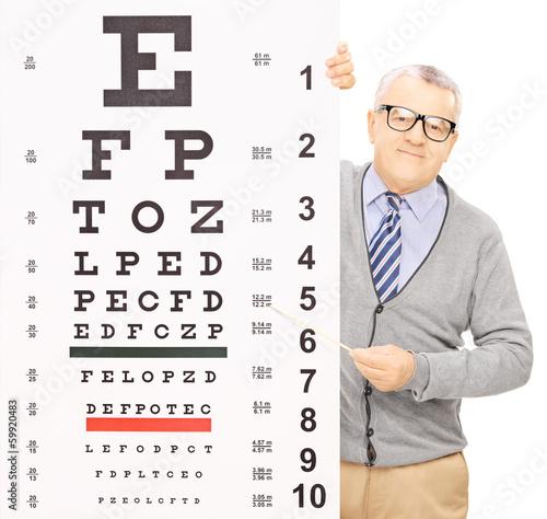 Fototapeta Senior man standing behind eyesight test pointing with a stick