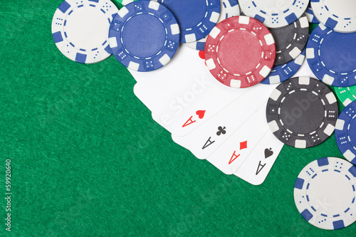 poker chips and playing cards on a green table background