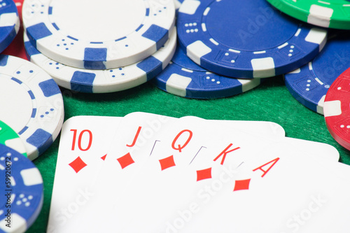 royal flush combination at poker with chips on the green table