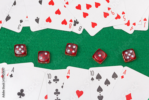 close up of playing cards and red dices on the green table