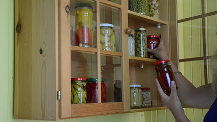girl from kitchen dresser takes jars pickled peppers tomatoes