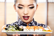 Beautiful young woman eating sushi. Shallow depth of field, focu