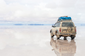 Car moving on Salar de Uyuni lake in Bolivia