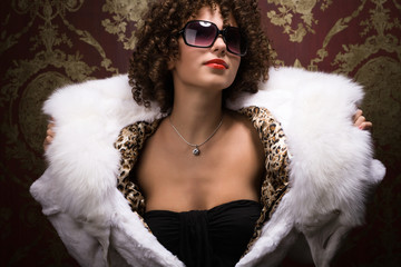 Portrait of beautiful curly young girl in furs