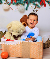 Laughing baby in the box with a bear in a Christmas setting