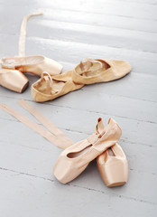Ballet shoes lay alone on the floor
