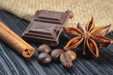 Chocolate bar and spices on wooden table