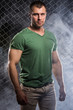 Fitness. Beautiful, strong man in clothes on fence background