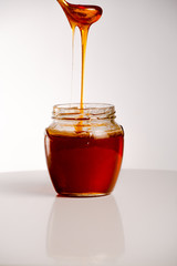 glass of fresh honey on white background