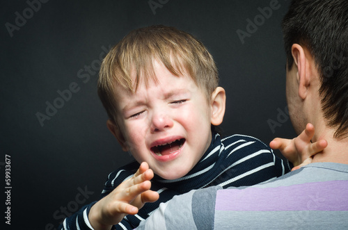 Portrait of a crying child on hands a father